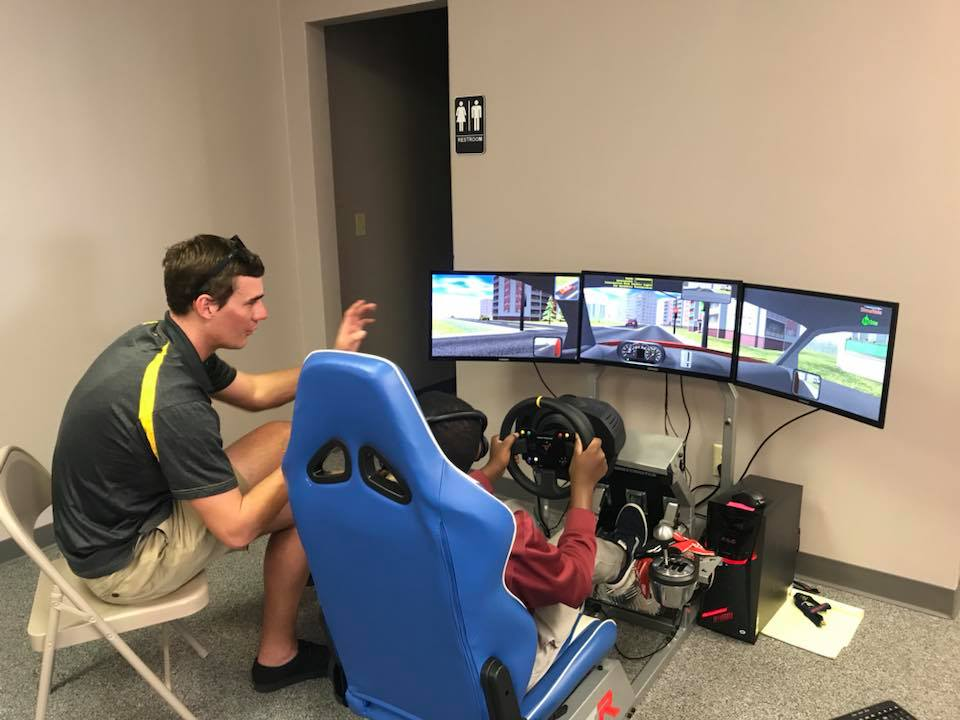 child driving car on simulator
