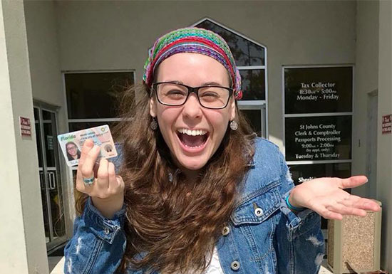 happy girl showing license after licensing requirements